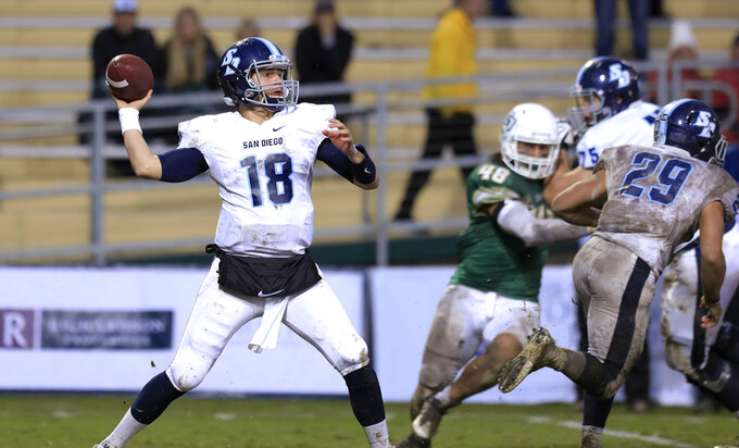 FILE - In this Nov. 26, 2016, file photo, San Diego quarterback Anthony Lawrence (18) looks for a receiver during the second quarter against Cal Poly in an NCAA FCS first-round playoff game in San Luis Obispo, Calif. The University of San Diego is in the FCS playoffs for the third straight year under 75-year-old coach Dale Lindsey and senior quarterback Anthony Lawrence. It's a terrific accomplishment, considering that the Toreros don't offer football schoarlships and it costs $65,426 a year to attend the small Catholic school known for its Spanish Renaissance architecture and a million-dollar view of Mission Bay and the Pacific Ocean. (Laura Dickinson/The Tribune (of San Luis Obispo) via AP, File)