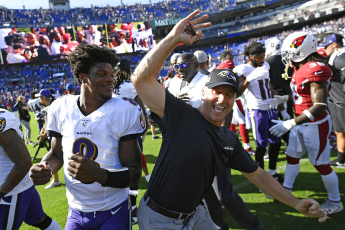 Baltimore Ravens quarterback Lamar Jackson, left, celebrates with head coach John Harbaugh after an NFL football game against the Arizona Cardinals, Sunday, Sept. 15, 2019, in Baltimore. Baltimore won 23-17. (AP Photo/Nick Wass)
