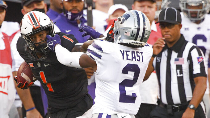 Kansas State defensive back Russ Yeast (2) grabs the face mask of Oklahoma State wide receiver Tay Martin (1) during the first half of an NCAA college football game Saturday, Sept. 25, 2021, in Stillwater, Okla. (AP Photo/Brody Schmidt)