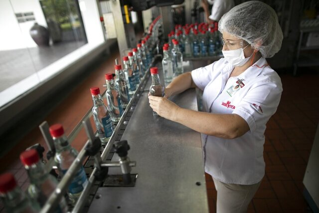 A worker inspects bottles of antiseptic alcohol at the Santa Teresa rum factory in La Victoria, Aragua state, Venezuela, Wednesday, April 1, 2020. Venezuela's premier rum distillery and one of Venezuela's few private businesses says that most of its production will be for antiseptic alcohol, in an effort to help contain the spread of the new coronavirus. (AP Photo/Ariana Cubillos)