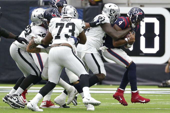 Houston Texans quarterback Deshaun Watson (4) is hit by Oakland Raiders defensive end Benson Mayowa (91) during the first half of an NFL football game Sunday, Oct. 27, 2019, in Houston. (AP Photo/Michael Wyke)