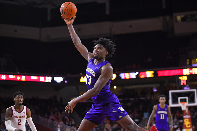 Washington forward Isaiah Stewart, center, shoots as Southern California guard Jonah Mathews, left, watches during the second half of an NCAA college basketball game Thursday, Feb. 13, 2020, in Los Angeles. (AP Photo/Mark J. Terrill)