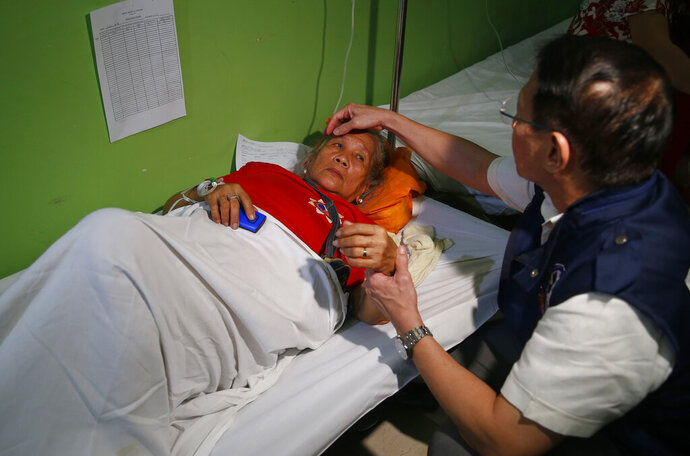 Philippine Health Secretary Francisco Duque III talks to patients who fell ill during the 90th birthday celebration of former Philippine First Lady Imelda Marcos, the flamboyant wife of the late dictator Ferdinand Marcos, Wednesday, July 3, 2019, in Manila, Philippines. Officials say more than 240 people have been brought to hospitals due to suspected food poisoning in the event which was attended by more than a thousand