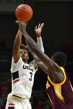 Connecticut's Alterique Gilbert shoots over Iona's Mo Thiam, right, in the second half of an NCAA college basketball game, Wednesday, Dec. 4, 2019, in Storrs, Conn. (AP Photo/Jessica Hill)
