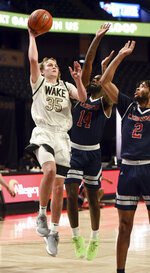 Wake Forest's Carter Whitt (35) shoots over Catawba's Taqwain Drummond (14) and Todd Burt (2) during an NCAA college basketball game, Thursday, Dec. 31, 2020, at Joel Coliseum in Winston-Salem, N.C. (Walt Unks//The Winston-Salem Journal via AP)