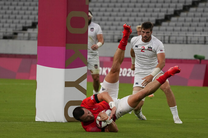 Britain's Alex Davis scores a try as Brett Thompson of the United States looks on, in their men's rugby sevens quarterfinal match at the 2020 Summer Olympics, Tuesday, July 27, 2021 in Tokyo, Japan. (AP Photo/Shuji Kajiyama)
