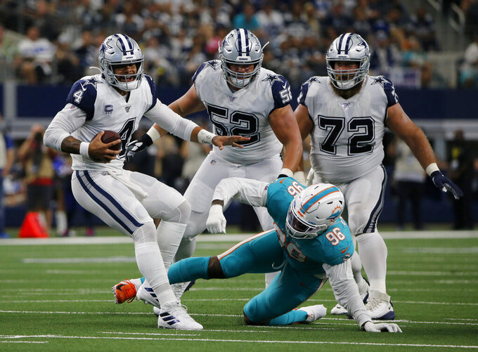 Dallas Cowboys quarterback Dak Prescott (4) escapes pressure from Miami Dolphins' Taco Charlton (96) in the first half of an NFL football game in Arlington, Texas, Sunday, Sept. 22, 2019. (AP Photo/Michael Ainsworth)