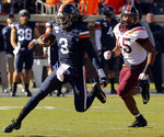 Virginia quarterback Bryce Perkins (3) runs the ball past Virginia Tech defender TyJuan Garbutt (45) during an NCAA college football game Friday, Nov. 29, 2019, in Charlottesville Va. (Matt Gentry/The Roanoke Times via AP)