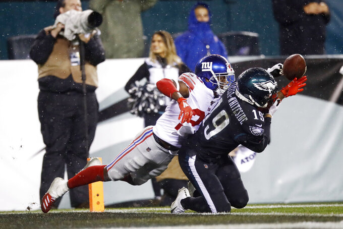 FILE - New York Giants' Deandre Baker, left, breaks up a pass intended for Philadelphia Eagles' J.J. Arcega-Whiteside during the second half of an NFL football game,in a  Monday, Dec. 9, 2019 file photo, in Philadelphia. New York Giants cornerback DeAndre Baker, Seattle Seahawks cornerback Quinton Dunbar and Washington receiver Cody Latimer have been put on the NFL's Commissioner Exempt List while facing felony charges from offseason incidents. (AP Photo/Matt Rourke, File)
