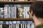 Lewis Peterson, co-owner of Four Star Video Cooperative, talks about some of the foreign video titles the store offers on State Street in Madison, Wis., Monday, Aug. 19, 2019.(Amber Arnold/Wisconsin State Journal via AP)