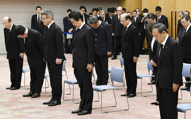 Japanese Prime Minister Shinzo Abe, center, observes a moment of silence at 2:46 p.m. when a magnitude 9.0 earthquake struck off Japan's northeastern coast nine years ago, at the prime minister's office in Tokyo, Wednesday, March 11, 2020. (Yoshitaka Sugawara/Kyodo News via AP)