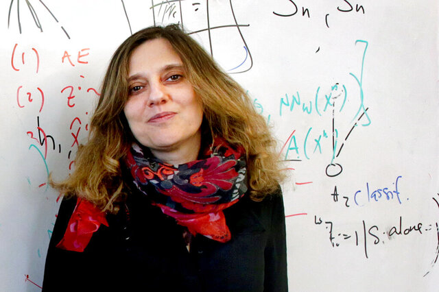 In this April 5, 2017, photo, Regina Barzilay, a professor in the Massachusetts Institute of Technology's Computer Science and Artificial Intelligence Laboratory, poses at MIT in Cambridge, Mass. The world's biggest AI society awarded Barzilay its top prize on Wednesday, Sept. 23, 2020. MIT said Barzilay is a breast cancer survivor whose 2014 diagnosis led her to shift her machine-learning work to creating systems for drug development and early cancer diagnosis. (Jonathan Wiggs/The Boston Globe via AP)