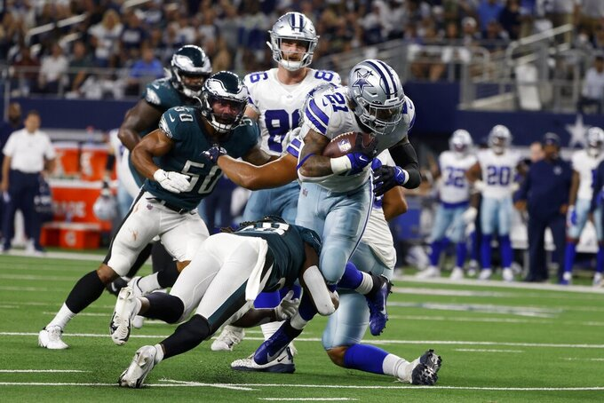 Dallas Cowboys running back Ezekiel Elliott (21) breaks a tackle attempt by Philadelphia Eagles safety Anthony Harris, bottom left, as he sprints to the end zone for a touchdown in the first half of an NFL football game in Arlington, Texas, Monday, Sept. 27, 2021. (AP Photo/Michael Ainsworth)