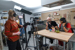 In this Oct. 7, 2020 photo, producer Jessica Opon, left, films Andrew Rea, founder of the Binging with Babish network, center, as he tastes popcorn ice cream created by chef Sohla El-Waylly, during a taping of the