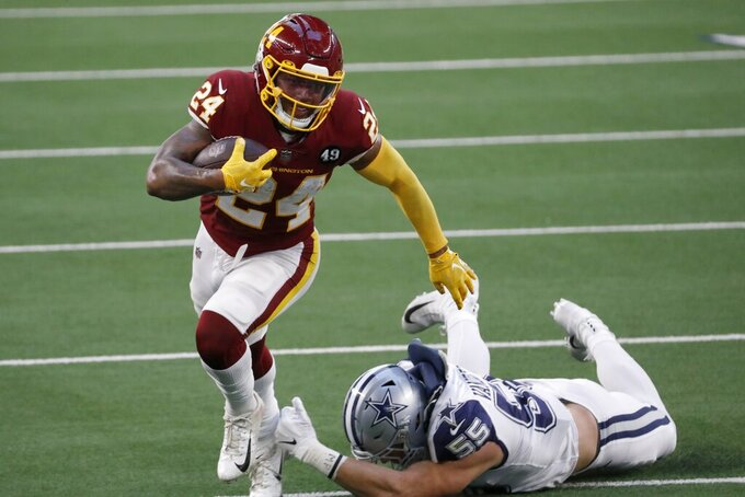 Washington Football Team running back Antonio Gibson (24) escapes a tackle attempt by Dallas Cowboys linebacker Leighton Vander Esch (55) in the first half of an NFL football game in Arlington, Texas, Thursday, Nov. 26, 2020. (AP Photo/Roger Steinman)