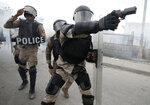 In this Oct. 4, 2019 photo, a police officer aims his weapon after demonstrators calling for the resignation of Haitian President Jovenel Moise broke through their lines, in Port-au-Prince, Haiti. After a two-day respite from the recent protests that have wracked Haiti's capital, opposition leaders urged citizens angry over corruption, gas shortages, and inflation to join them for a massive protest march to the local headquarters of the United Nations. (AP Photo/Rebecca Blackwell)