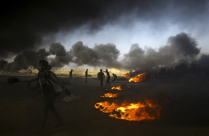 """FILE - In this Tuesday, May 15, 2018 file photo, Palestinian protesters burn tires at the Gaza Strip's border with Israel, east of Khan Younis. The aftershocks of the U.S. Embassy move to Jerusalem and bloodshed on the Gaza border are shaking up the region, including the relationship between Palestinian President Mahmoud Abbas and former his negotiating partners, Israel and the U.S. Seething over a perceived U.S. betrayal on Jerusalem, Abbas is preparing to pursue what has been called his """"doomsday weapon,"""" a war crimes complaint against Israel at the International Criminal Court. (AP Photo/Adel Hana, File)"""