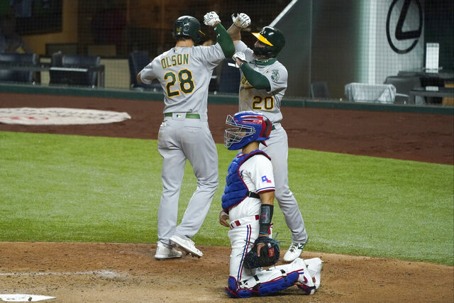 Oakland Athletics' Matt Olson (28) and Mark Canha (20) celebrate a two-run home run by Olson that scored Canha as Texas Rangers catcher Robinson Chirinos kneels by the plate in the fourth inning of a baseball game in Arlington, Texas, Tuesday, Aug. 25, 2020. (AP Photo/Tony Gutierrez)