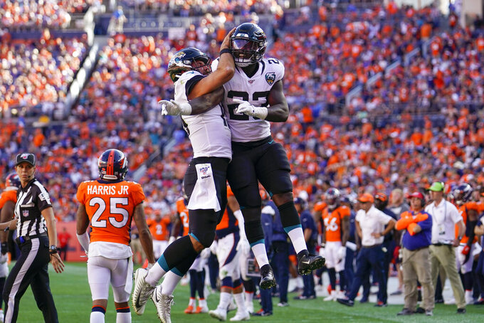 Jacksonville Jaguars running back Ryquell Armstead, right, celebrates with quarterback Gardner Minshew after scoring a touchdown during the second half of an NFL football game against the Denver Broncos, Sunday, Sept. 29, 2019, in Denver. (AP Photo/Jack Dempsey)