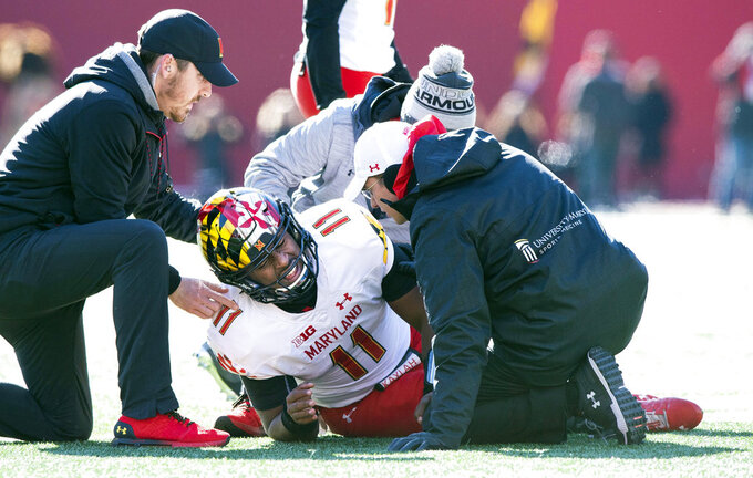 FILE - In this Nov. 10, 2018, file photo, Maryland quarterback Kasim Hill (11) grimaces as he is examined by team trainers after an apparent injury during the first half of an NCAA college football game against Indiana, in Bloomington, Ind. With No. 9 Ohio State next on the schedule, Maryland has yet another obstacle to overcome. Interim coach Matt Canada announced Tuesday, Nov. 13, 2018, that starting quarterback Kasim Hill tore the ACL in his left knee against Indiana last week, making this the second straight season he's had cut short with a knee injury. Tyrrell Pigrome will start against the Buckeyes (9-1, 6-1 Big Ten) as Maryland (5-5, 3-4) tries for a third straight week to get a win that will make them bowl eligible. (AP Photo/Doug McSchooler, File)