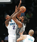 Charlotte Hornets forward Marvin Williams (2) and guard Nicolas Batum (5) defend as Brooklyn Nets center DeAndre Jordan (6) shoots during the first half of an NBA basketball game Wednesday, Nov. 20, 2019, in New York. (AP Photo/Kathy Willens)