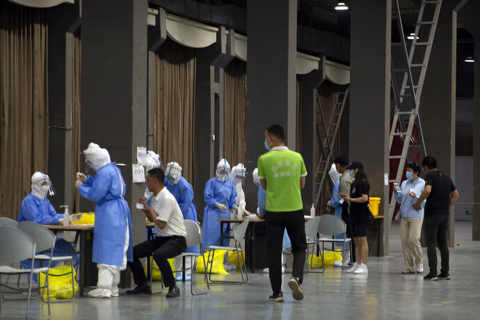 Workers in protective suits administer coronavirus tests at a COVID-19 testing site for those who were potentially exposed to the coronavirus at a wholesale food market in Beijing, Wednesday, June 17, 2020. As the number of cases of COVID-19 in Beijing climbed in recent days following an outbreak linked to a wholesale food market, officials announced they had identified hundreds of thousands of people who needed to be tested for the coronavirus. (AP Photo/Mark Schiefelbein)