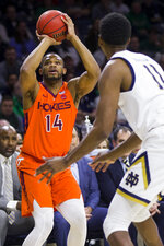 Virginia Tech's P.J. Horne (14) shoots a 3-pointer in front of Notre Dame's Juwan Durham (11) during the first half of an NCAA college basketball game Saturday, March 7, 2020, in South Bend, Ind. (AP Photo/Robert Franklin)