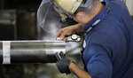 FILE- In this June 5, 2018, file photo Erik Cordova inspects a steel pipe at the Borusan Mannesmann Pipe manufacturing facility Tuesday, June 5, 2018, in Baytown, Texas. On Friday, Sept. 14, the Federal Reserve reports on U.S. industrial production for August. (AP Photo/David J. Phillip, File)