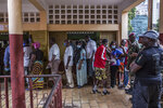 People line up to vote at the Boulbinet Deaf School in Conakry, Guinea, Sunday Oct. 18, 2020. Guinean President Alpha Conde is seeking to extend his decade in power, facing off against his longtime rival Cellou Dalein Diallo for the third time at the polls. (AP Photo/Sadak Souici)