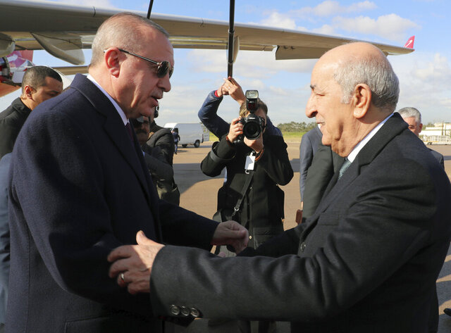Algeria's President Abdelmadjid Tebboune, right, and Turkey's President Recep Tayyip Erdogan greet each other during a welcoming ceremony at the airport, in Algiers, Algeria, Sunday, Jan. 26, 2020. Erdogan is in Algeria as first step of his three-nation Africa tour.(Turkish Presidency via AP, Pool)