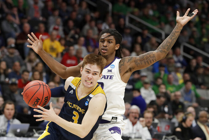 UC Irvine guard Robert Cartwright (3) drives past Kansas State guard Cartier Diarra during the second half a first-round game in the NCAA men's college basketball tournament Friday, March 22, 2019, in San Jose, Calif. (AP Photo/Chris Carlson)