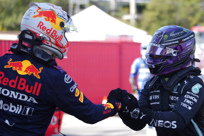 Mercedes driver Lewis Hamilton of Britain, right, shakes hands with Red Bull driver Max Verstappen of the Netherlands after clocking the fastest time in the qualifying for the Spanish Formula One Grand Prix at the Barcelona Catalunya racetrack in Montmelo, just outside Barcelona, Spain, Saturday, May 8, 2021. The Spanish Grand Prix will be held on Sunday. Verstappen clocked the second fastest time. (AP Photo/Emilio Morenatti, Pool)