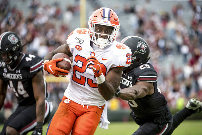 Clemson running back Lyn-J Dixon (23) carries the ball against South Carolina defensive back J.T. Ibe (29) during the second half of an NCAA college football game Saturday, Nov. 30, 2019, in Columbia, S.C. Clemson defeated South Carolina 38-3. (AP Photo/Sean Rayford)