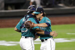 Seattle Mariners closing pitcher Taylor Williams, right, embraces catcher Austin Nola after the team beat the Oakland Athletics in a baseball game during the Mariners home opener Friday, July 31, 2020, in Seattle. The Mariners won 5-3.(AP Photo/Elaine Thompson)