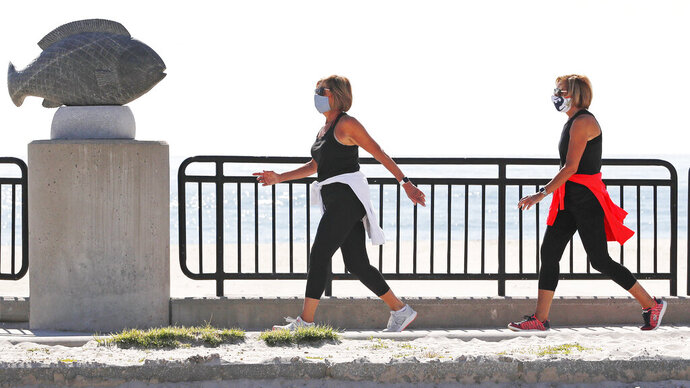 Two women, wearing protective masks due to the COVID-19 virus outbreak, walk on a sidewalk adjacent to an empty Hampton Beach in Hampton, N.H., Thursday, May 21, 2020. Beaches in New Hampshire have been closed since March by state order due to the coronavirus. (AP Photo/Charles Krupa)