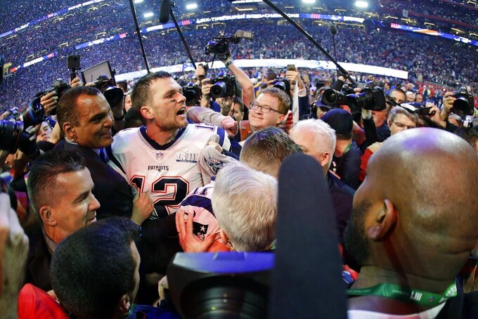 New England Patriots' Tom Brady (12) is surrounded by media on the field, after the NFL Super Bowl 53 football game against the Los Angeles Rams, Sunday, Feb. 3, 2019, in Atlanta. The Patriots won 13-3. (AP Photo/Mark Humphrey)