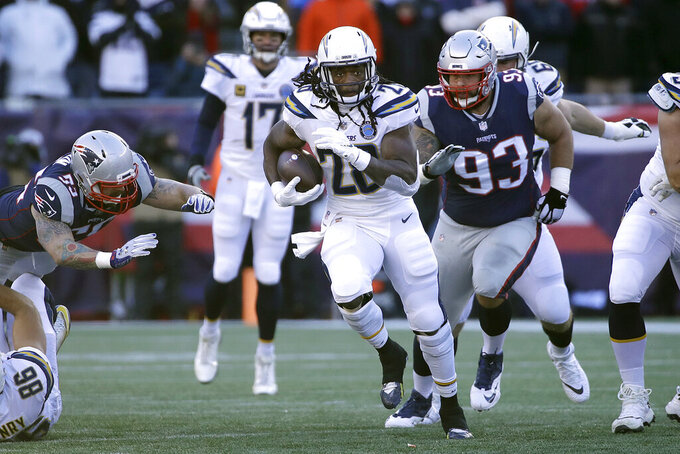 Los Angeles Chargers running back Melvin Gordon (28) runs from New England Patriots defensive tackle Lawrence Guy (93) during the first half of an NFL divisional playoff football game, Sunday, Jan. 13, 2019, in Foxborough, Mass. (AP Photo/Elise Amendola)
