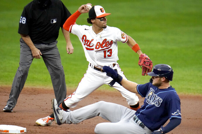 Baltimore Orioles shortstop Andrew Velazquez (13) forces out Tampa Bay Rays' Austin Meadows, bottom, at second base on a ball hit by Joey Wendle during the second inning of a baseball game, Thursday, Sept. 17, 2020, in Baltimore. (AP Photo/Julio Cortez)