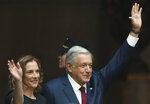 Mexico's President Andres Manuel Lopez Obrador and his wife Beatriz Gutierrez Muller wave goodbye after delivering his first year's state of the nation address at the National Palace in Mexico City, Sunday, Sept. 1, 2019. (AP Photo/Marco Ugarte)
