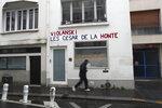 A man walks by the Academie des Cesar headquarters where a graffiti reads
