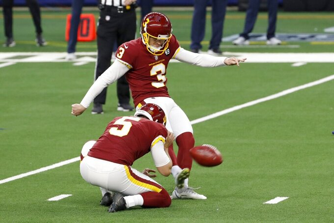 Washington Football Team punter Tress Way (5) holds the ball as place kicker Dustin Hopkins (3) kicks a field goal in the first half of an NFL football game against the Dallas Cowboys in Arlington, Texas, Thursday, Nov. 26, 2020. (AP Photo/Roger Steinman)