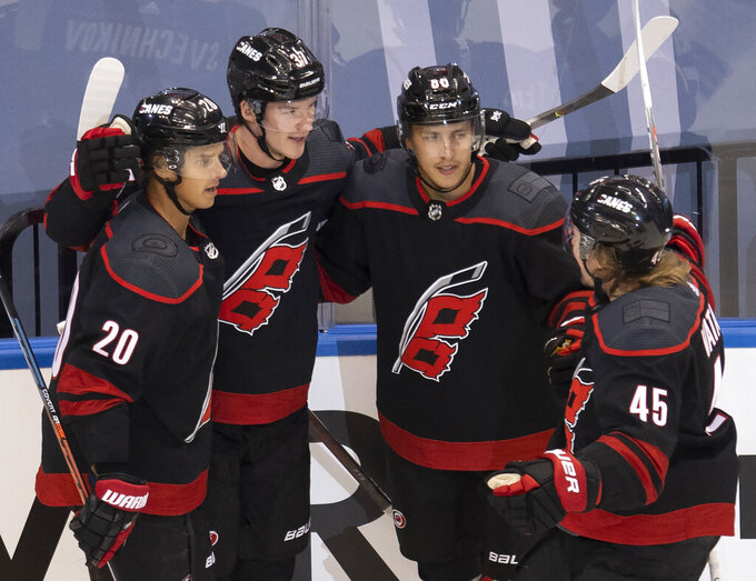 Carolina Hurricanes right wing Andrei Svechnikov (37) is congratulated teammates center Sebastian Aho (20), left wing Teuvo Teravainen (86) and defenseman Sami Vatanen (45) after scoring goal against the New York Rangers during the first period of an NHL Stanley Cup playoff hockey game in Toronto, Monday, Aug. 3, 2020. (Frank Gunn/The Canadian Press via AP)