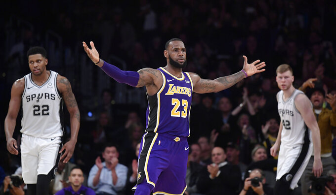 Los Angeles Lakers forward LeBron James, center, gestures after scoring as San Antonio Spurs forward Rudy Gay, left, and forward Davis Bertans, of Latvia, look on during the second half of an NBA basketball game, Wednesday, Dec. 5, 2018, in Los Angeles. The Lakers won 121-113. (AP Photo/Mark J. Terrill)