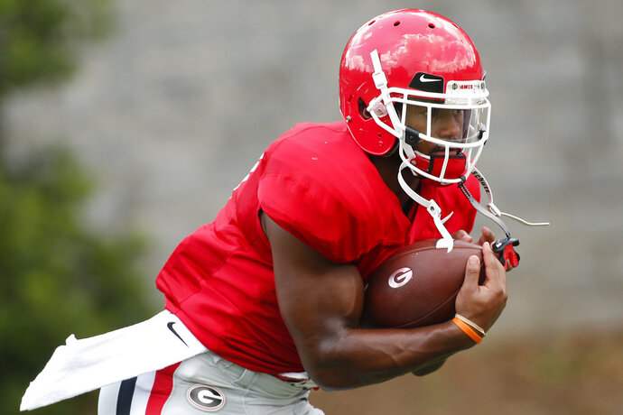FILE - In this Aug. 9, 2018, file photo, Georgia running back D'Andre Swift (7) runs a drill during a NCAA college football practice in Athens, Ga. Losing freshman tailback Zamir White, one of the Bulldogs' top recruits, to a knee injury in preseason practice forces No. 3 Georgia to recast its depth chart. It affirms D'Andre Swift as the favorite to be the top rusher and  also a reminder the Bulldogs had very few such injuries while winning the SEC and playing for the national championship last season. (Joshua L. Jones/Athens Banner-Herald via AP, File)