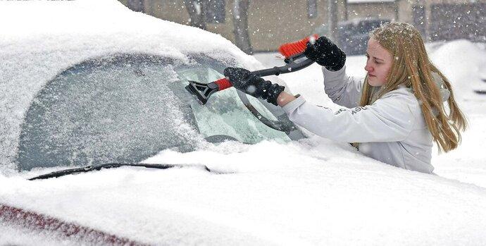 Madison Becker scrapes frozen sleet from her windshield as light, fluffy snow falls on Monday, Feb. 11, 2019, in Bismarck, N.D. (Tom Sromme/The Bismarck Tribune via AP)