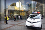 Chinese police sit in their vehicle as it is parked outside an Apple store at an outdoor shopping area in Beijing, Tuesday, Sept. 25, 2018. A Chinese trade envoy said Tuesday that talks with Washington are impossible while the United States