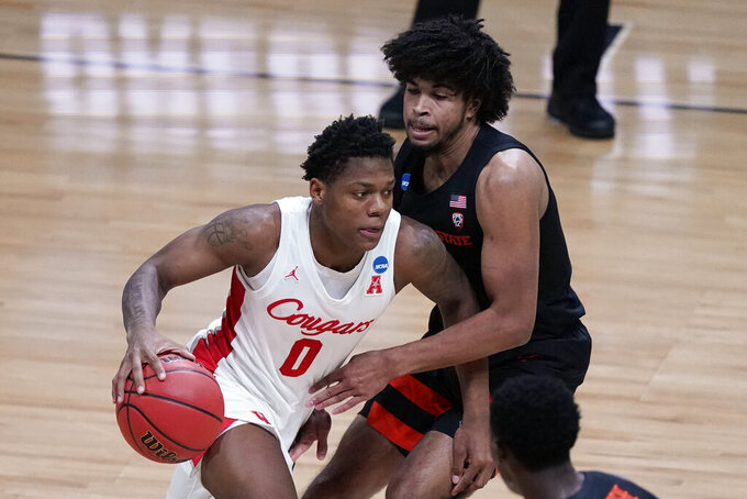 Houston guard Marcus Sasser (0) drives on Oregon State guard Ethan Thompson, right, during the first half of an Elite 8 game in the NCAA men's college basketball tournament at Lucas Oil Stadium, Monday, March 29, 2021, in Indianapolis. (AP Photo/Michael Conroy)