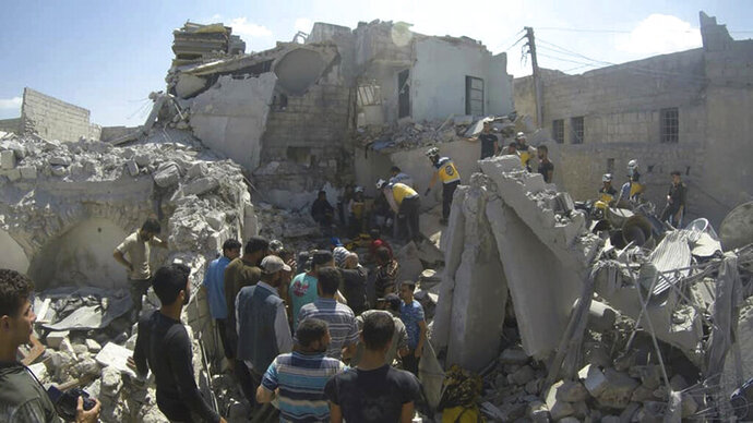 This photo provided by the Syrian Civil Defense White Helmets, which has been authenticated based on its contents and other AP reporting, shows Syrian White Helmet civil defense workers search for victims from under the rubble of a destroyed building that hit by a Syrian government airstrike, in the northern town of Ariha, in Idlib province, Syria, Friday, July 12, 2019. (Syrian Civil Defense White Helmets via AP)