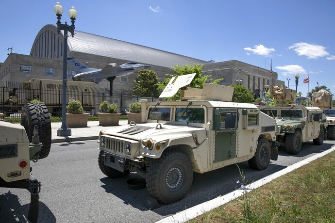 FILE - In this June 1, 2020, file photo, vehicles for the District of Columbia National Guard are seen outside the D.C. Armory in Washington. A peaceful protest in a sleepy suburb that's home to the head of the California National Guard was among four demonstrations monitored by National Guard spy planes. That's according to a report by the Los Angeles Times. The four spy planes took to the skies over cities in June to monitor protests following the killing of George Floyd. Three watched demonstrations in Minneapolis, Phoenix, and Washington, D.C. But the target of the fourth was the Sacramento, Calif., suburb of El Dorado Hills. (AP Photo/Jacquelyn Martin, File)