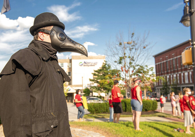Jim Dudevior a custodian at Sherwood Heights Elementary School wears a plague doctor costume during a stand-in by the Auburn Schools faculty and staff outside of City Hall in Auburn, Maine on Wednesday, Aug. 12, 2020. (Andree Kehn/Sun Journal via AP)